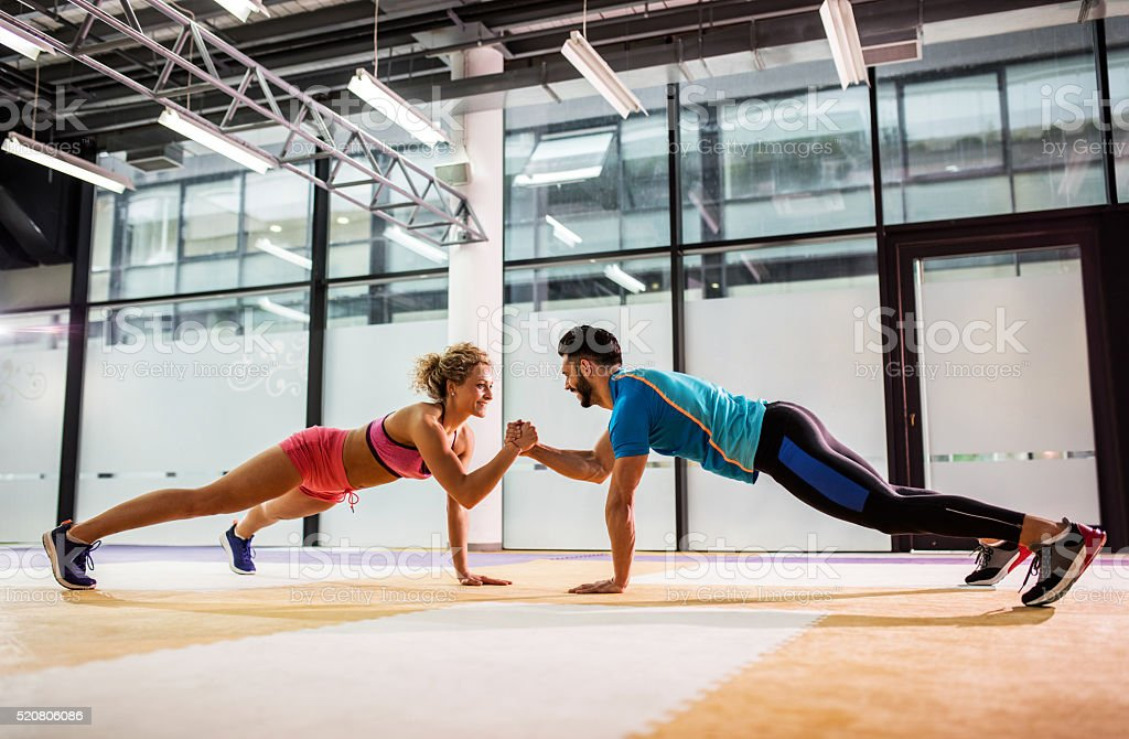 Smiling couple doing push-ups together in a gym. stock photo