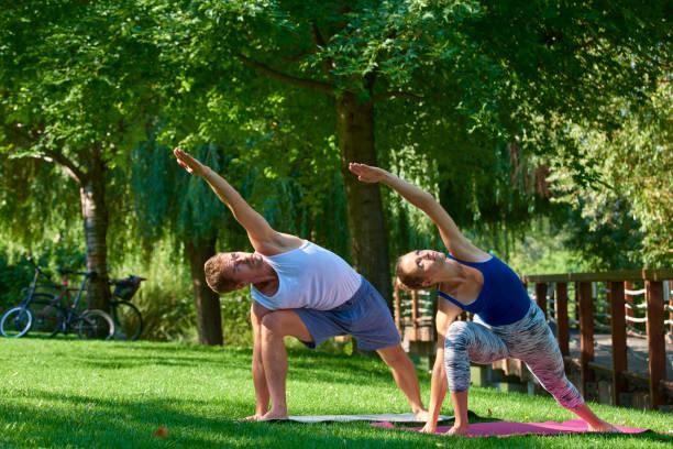 Lächelnde Paar, die Yoga-Übungen im Freien macht – Foto