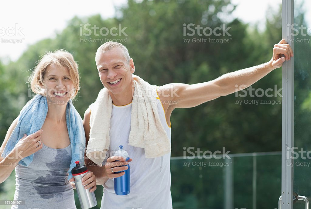Smiling couple drinking water after exercise stock photo