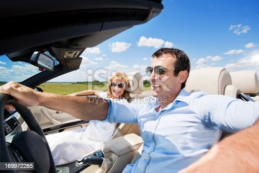 627863858istockphoto Smiling couple driving in the cabriolet car. 169972285