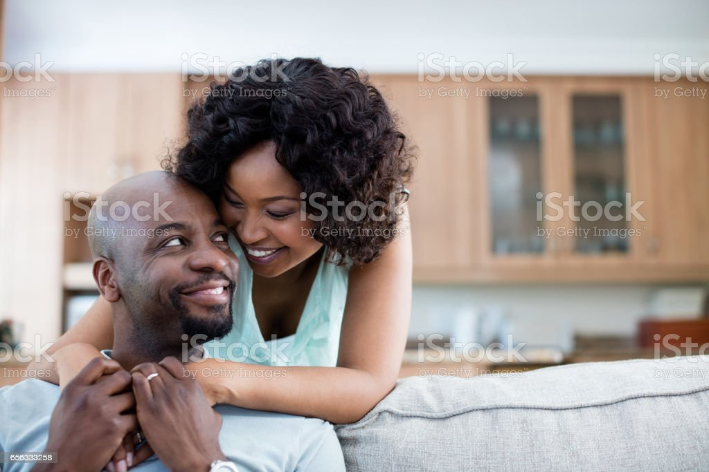Smiling couple embracing each other in living room stock photo