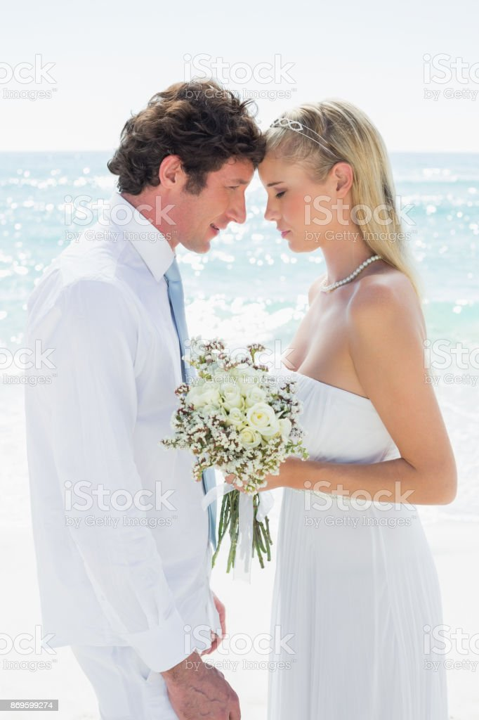 Smiling couple embracing each other on their wedding day stock photo