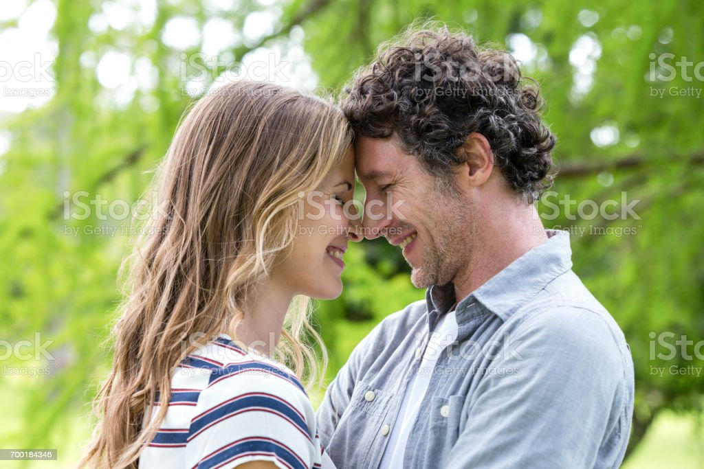 Smiling couple embracing head to head stock photo