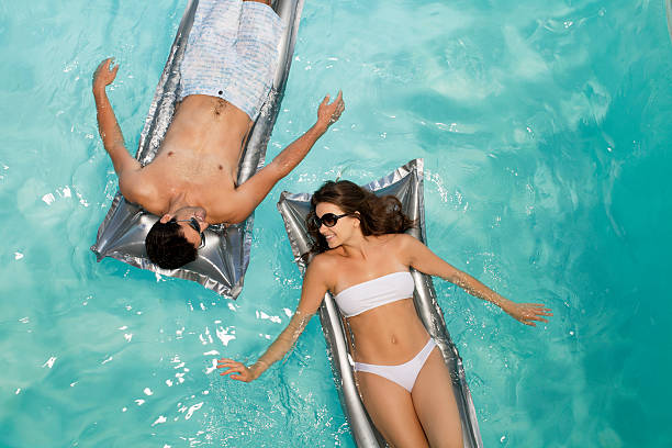Smiling couple floating in pool  floating on water stock pictures, royalty-free photos & images