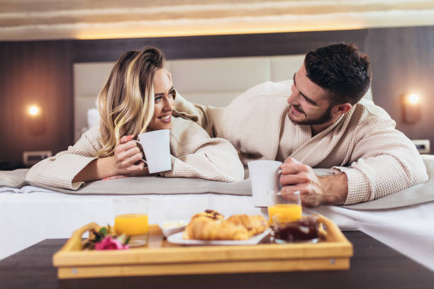Smiling couple having breakfast in bed in hotel room stock photo