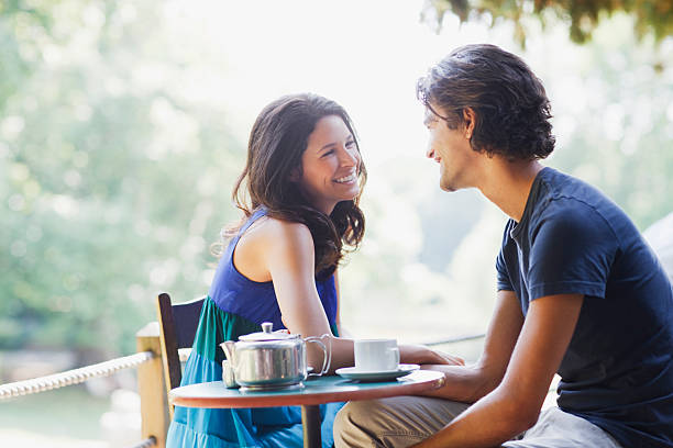 smiling couple having tea outdoors - dating stock photos and pictures