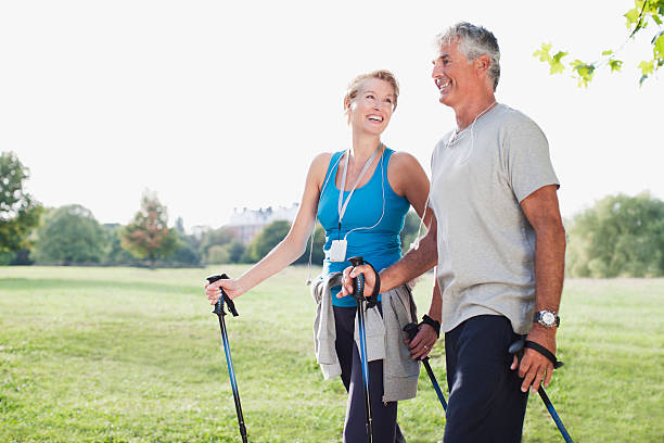 Smiling couple hiking together  nordic walking stock pictures, royalty-free photos & images