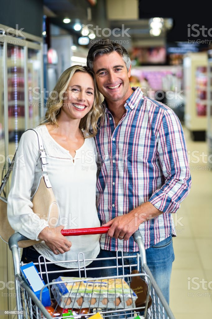 Smiling couple holding cart foto stock royalty-free