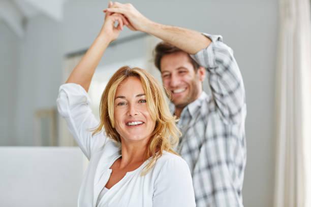Lächelndes Paar hält Hände und tanzt zusammen zu Hause – Foto