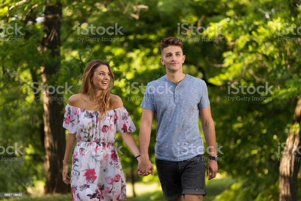 Smiling couple holding hands and walking in park. - Стоковые фото Беззаботный роялти-фри