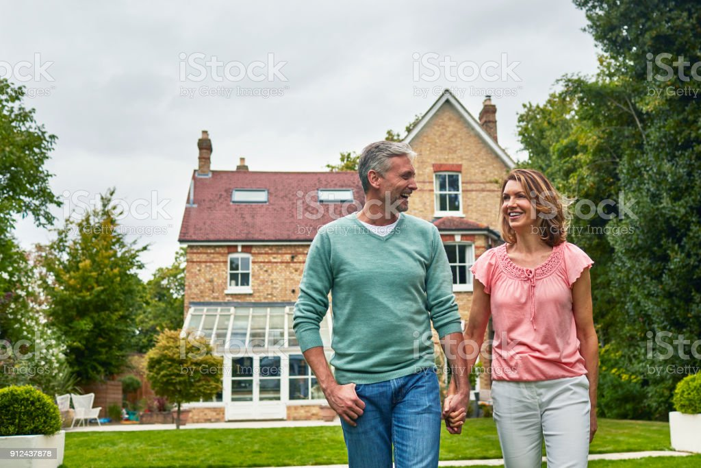 Smiling couple holding hands in front of house stock photo