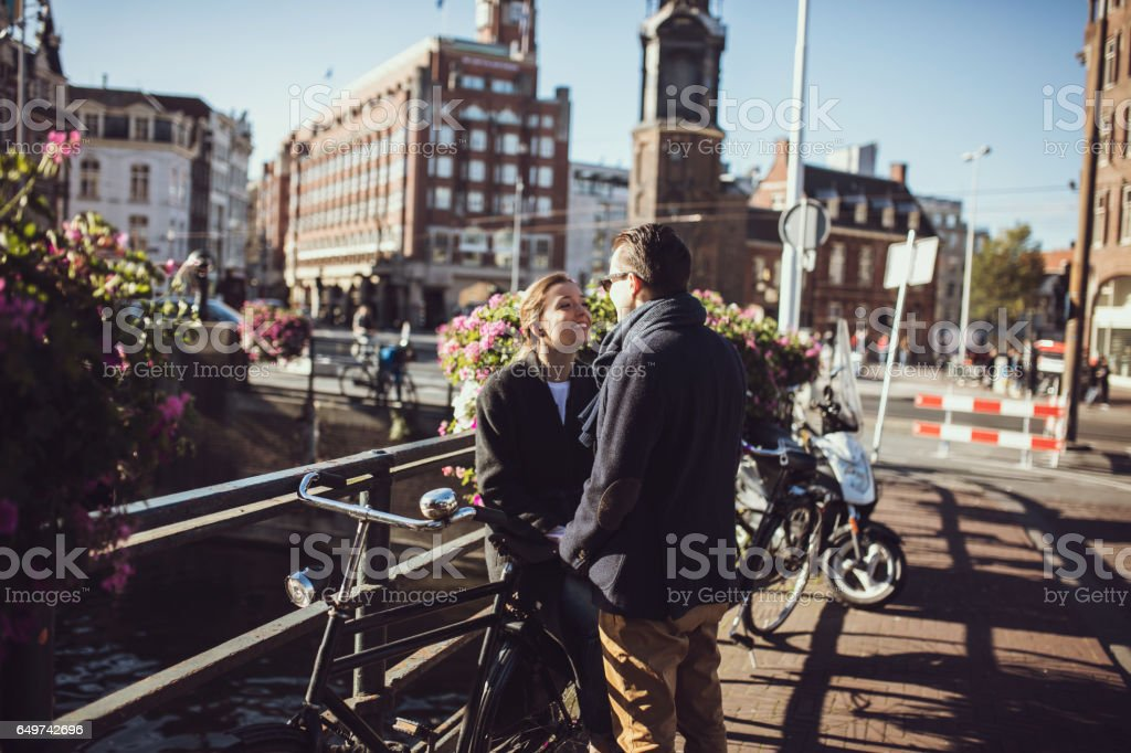 Smiling couple holding hands on the bridge, girl is sitting on the bicycle stock photo