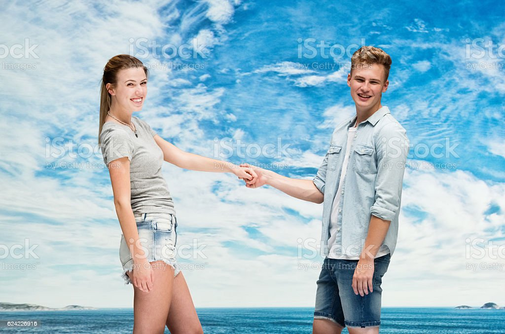 Smiling couple holding hands outdoors stock photo