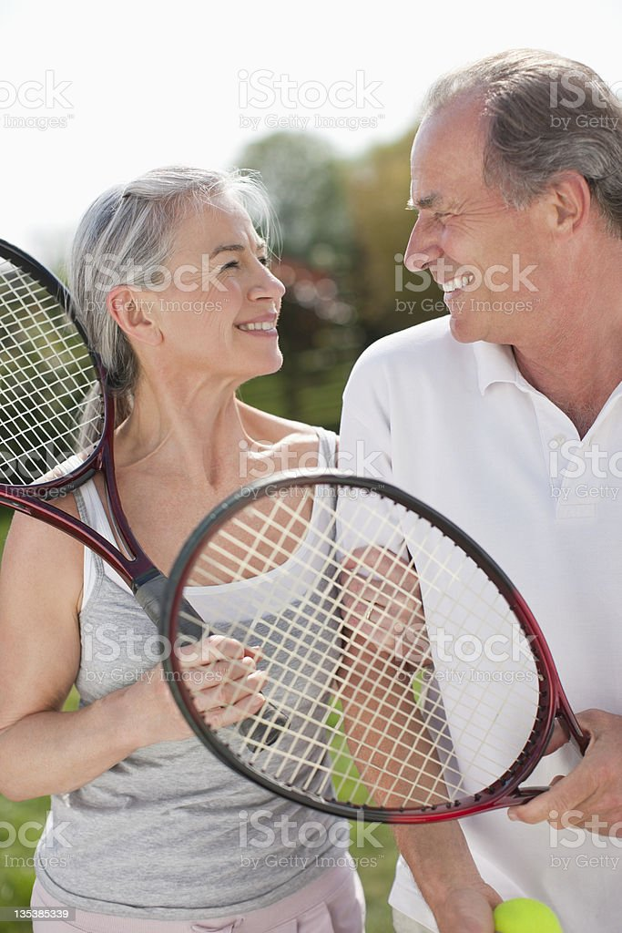 Smiling couple holding tennis rackets stock photo
