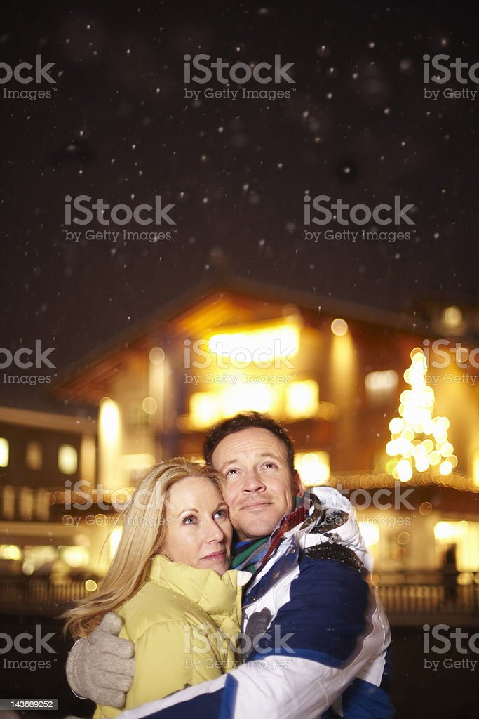 Smiling couple hugging in snow royalty-free stock photo