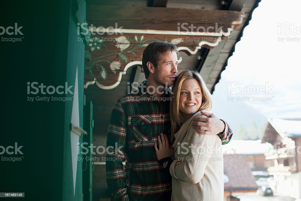 Smiling couple hugging on cabin porch royalty-free stock photo