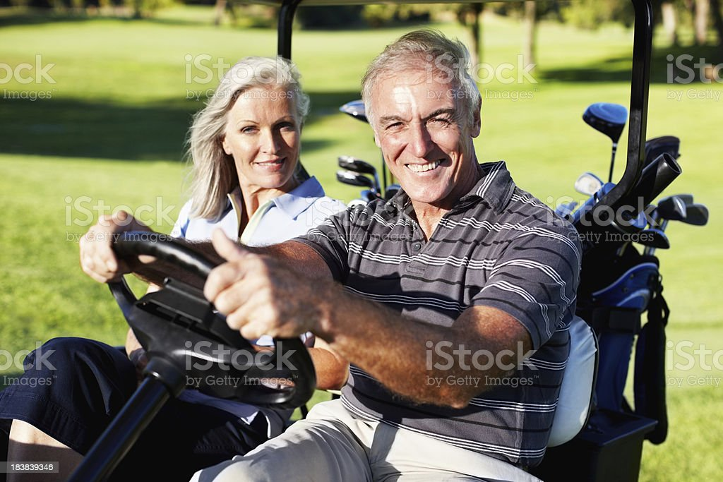 Smiling couple in a golf cart stock photo