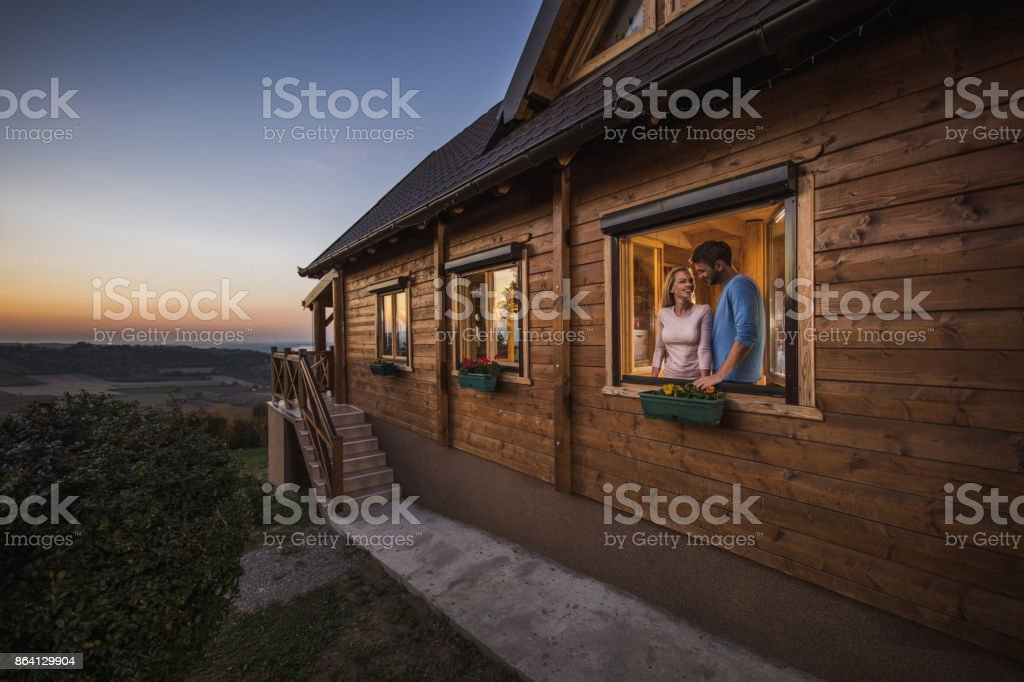 Smiling couple in love standing at the window in their cottage and talking. royalty-free stock photo