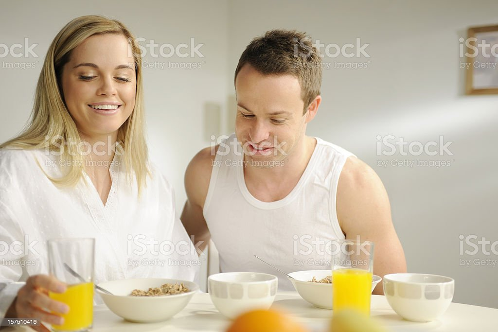 Smiling couple in night clothes having breakfast. royalty-free stock photo