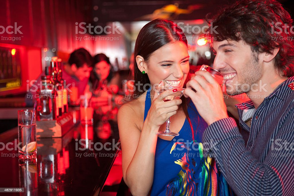 Smiling couple in nightclub with beverage stock photo