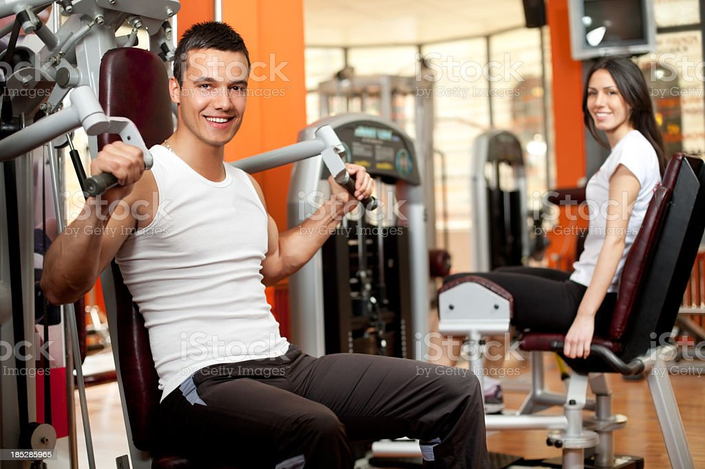 Smiling couple in white using the weight machines at the gym royalty-free stock photo