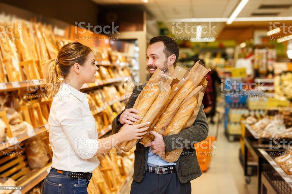 Sorrir casal é escolher a padaria no departamento de pão - foto de acervo
