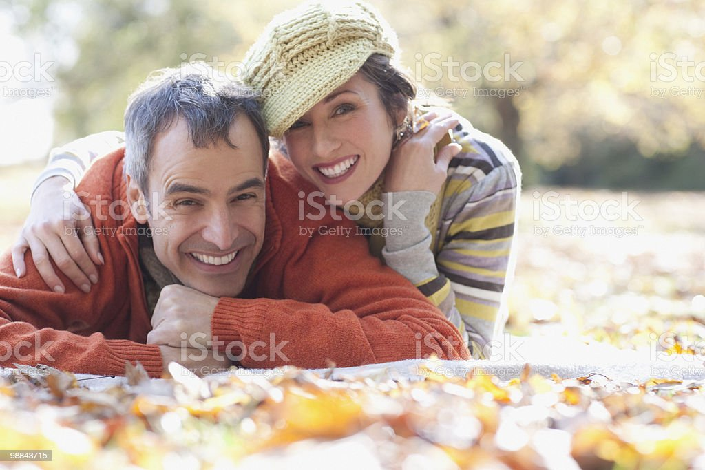 Smiling couple laying on autumn leaves royalty-free stock photo
