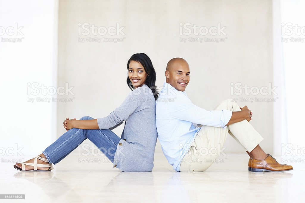 Smiling couple leaning against each other stock photo