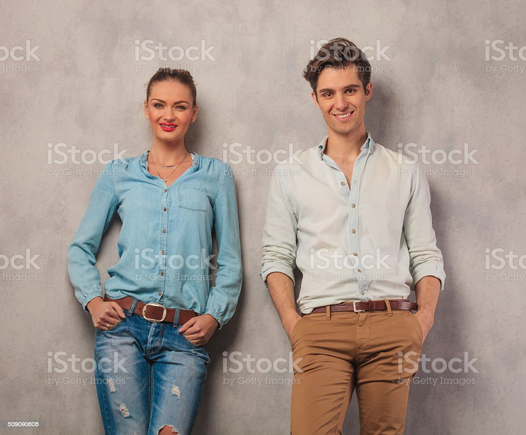 smiling couple leaning against the wall with hands in pockets stock photo