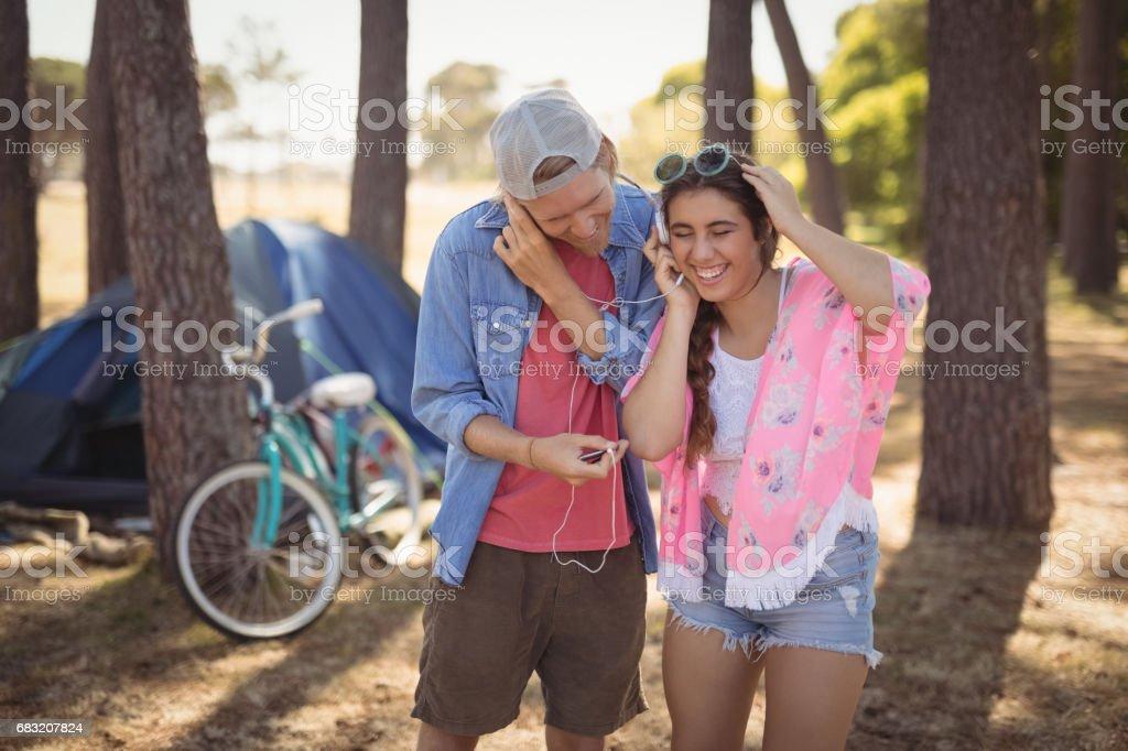 微笑夫婦對反對的樹木站立時耳機聽音樂 免版稅 stock photo