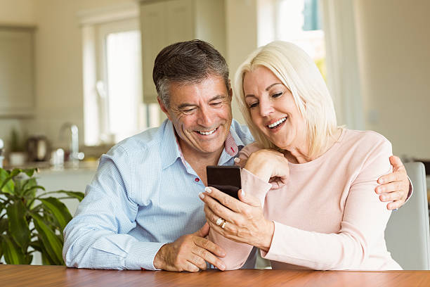 Smiling couple looking at a smartphone stock photo