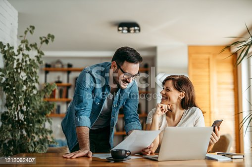 Smiling couple looking at documents at home office, portrait.