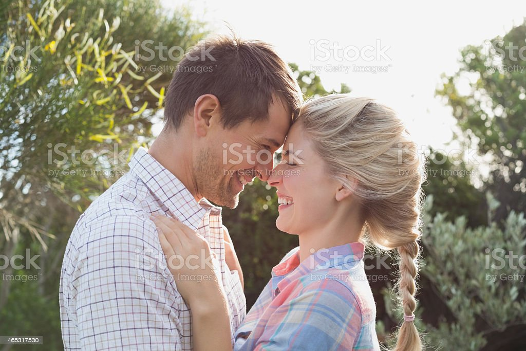 Smiling couple looking at each other against sky stock photo