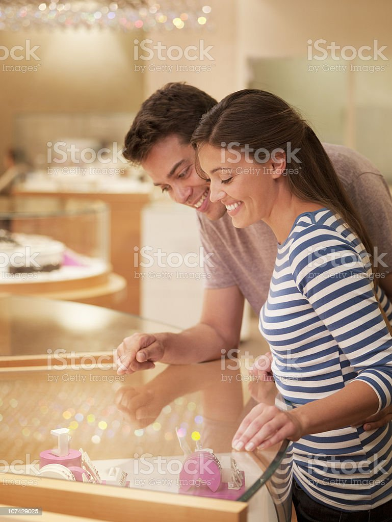 Smiling couple looking at jewelry case stock photo