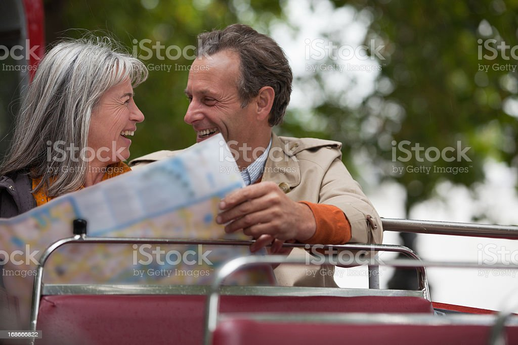 Smiling couple looking at map on double decker bus royalty-free stock photo