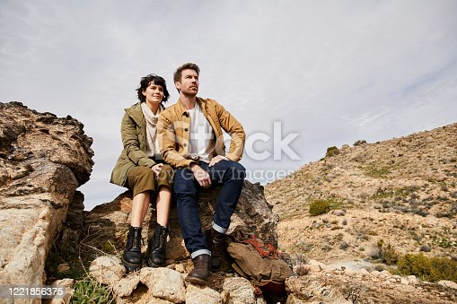 Smiling young couple looking at the scenic view while taking a break from their hike together in the countryside