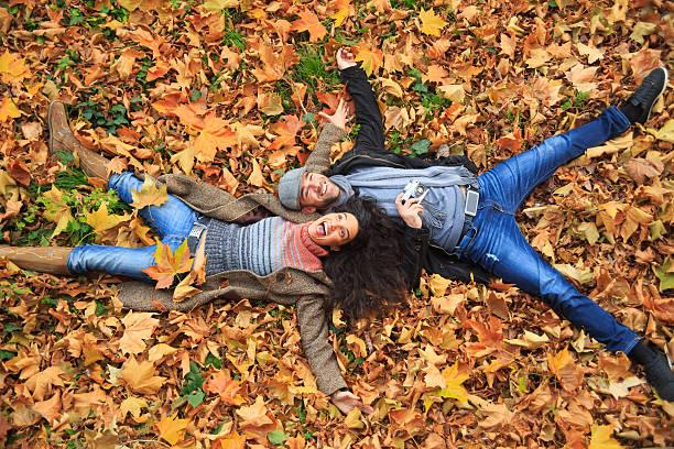 Casal sorridente deitado para baixo em folhas de carpete - foto de acervo