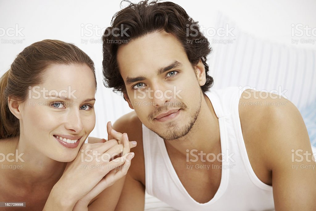 Smiling couple lying together on the bed royalty-free stock photo