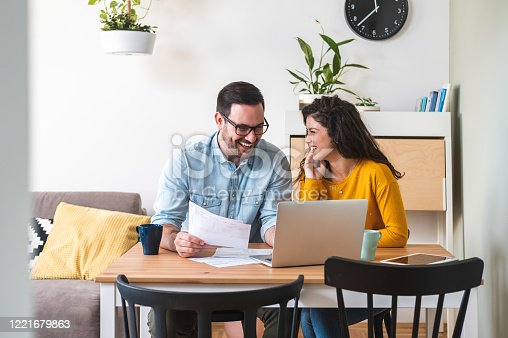 Happy husband and wife read good news online at laptop, smiling man holding documents receiving positive decision from bank