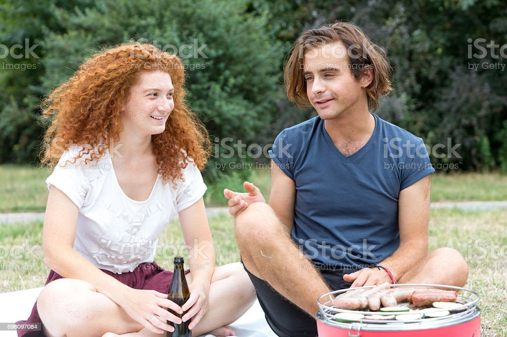 Smiling couple of young people having picnic in park royalty-free stock photo