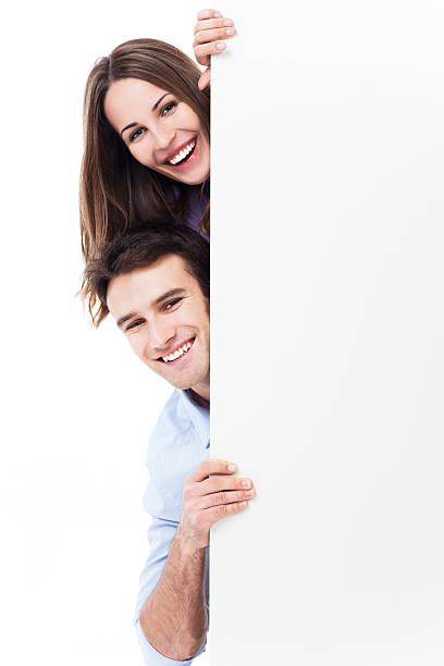 lächelnd paar spähen hinter plakat - heiratssprüche stock-fotos und bilder