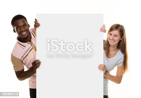 istock Smiling couple peeking behind placard, 835863748