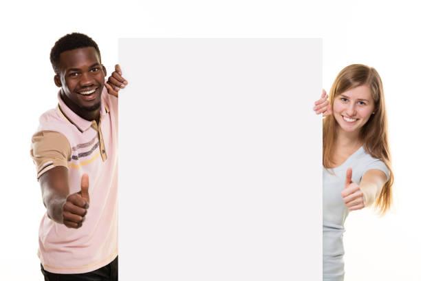 lächelnde paar spähen hinter plakat, - heiratssprüche stock-fotos und bilder