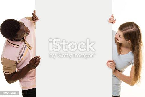 istock Smiling couple peeking behind placard, 835864412