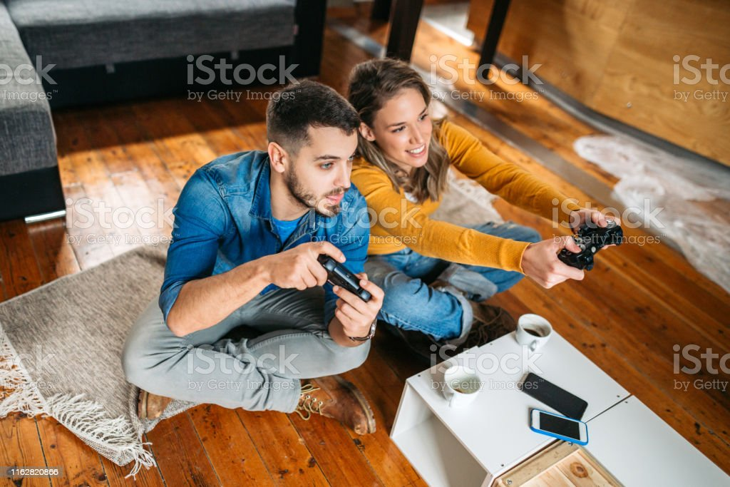 Smiling couple playing video games Young couple spending quality time together, playing video games, sitting on the floor, having fun Adult Stock Photo