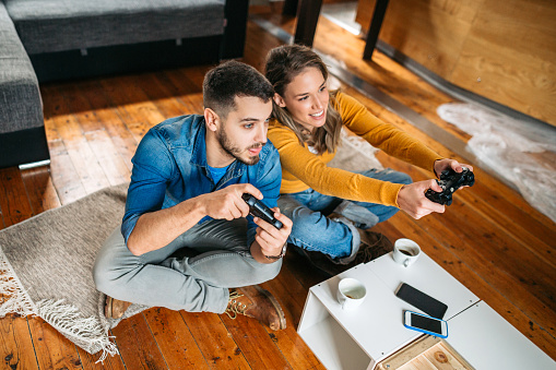 Smiling Couple Playing Video Games Stock Photo - Download Image Now