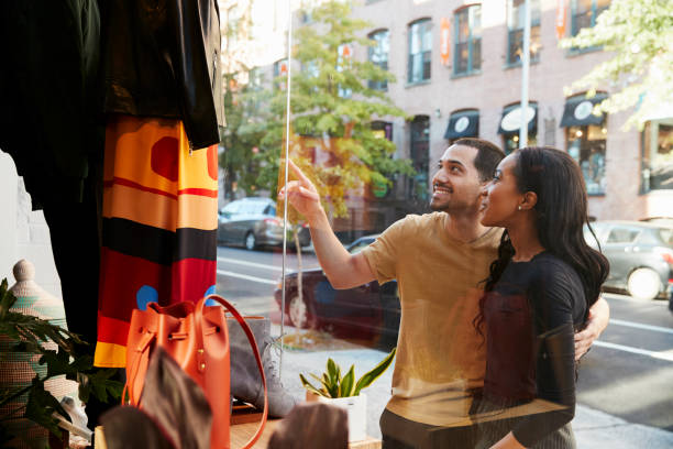 Smiling couple pointing at clothes in a shop window stock photo