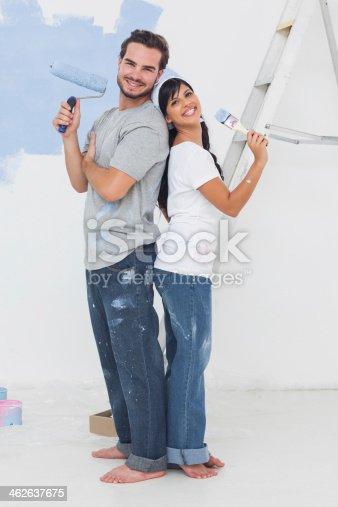 istock Smiling couple posing holding paintbrush 462637675