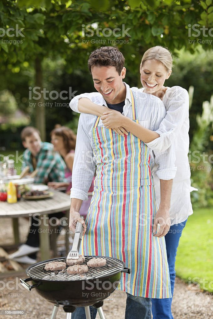 Smiling couple preparing food over barbecue in garden with people in background royalty-free stock photo