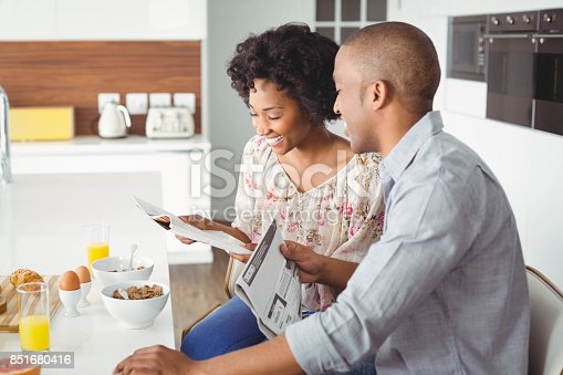 istock Smiling couple reading magazine and documents during breakfast 851680416
